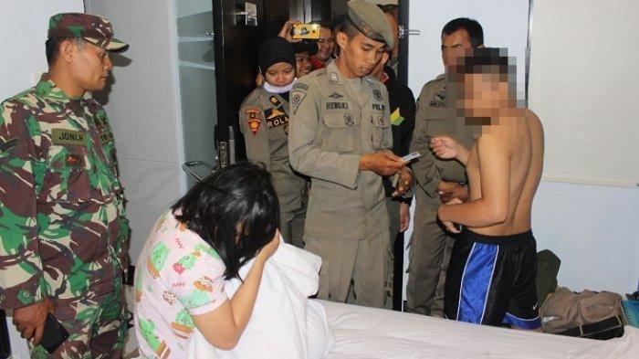 Petugas Satpol PP memeriksa identitas sepasang remaja yang ditemukan di sebuah kamar hotel di Padang, Minggu (3/11) dinihari.