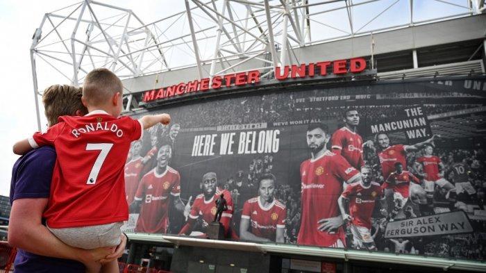Seorang fans muda yang mengenakan kaus pemain baru Manchester United, Cristiano Ronaldo, menunjuk ke stadion Old Trafford di Manchester, Inggris barat laut pada 6 September 2021.
