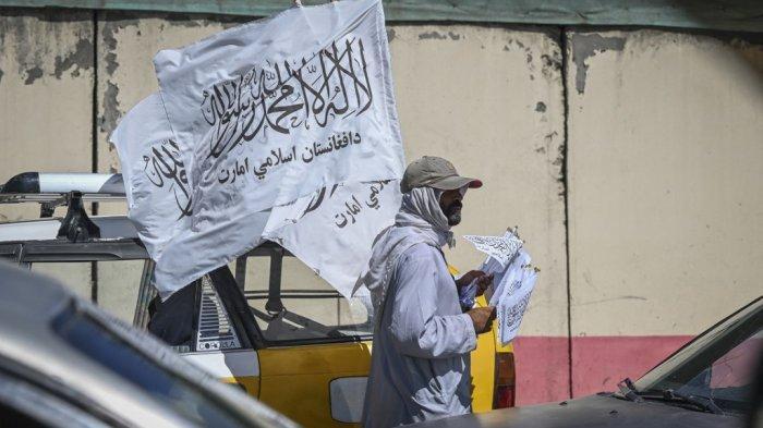 Seorang pedagang keliling membawa bendera Taliban saat para penumpang berjalan di sepanjang jalan di Kabul pada 5 September 2021.