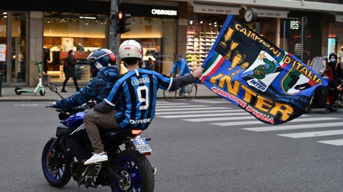 Seorang suporter Inter Milan dengan sepeda motor yang mengenakan seragam penyerang Belgia Inter Milan Romelu Lukaku mengibarkan bendera bertuliskan