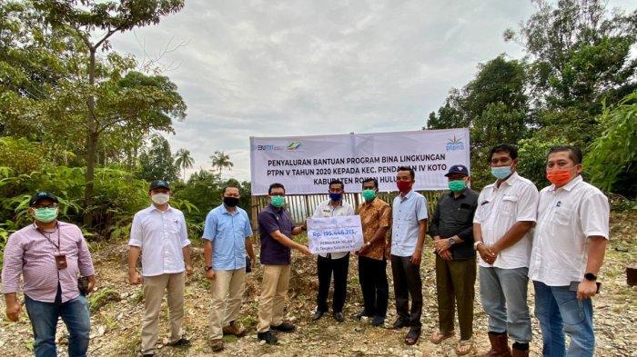 SEVP Business Support PTPN V Rurianto menyerahkan bantuan dana bina lingkungan untuk peningkatan kualitas jalan kepada Kepala Desa Pendalian Mulyadi, baru-baru ini di Kec. Pendalian IV Koto Rokan Hulu