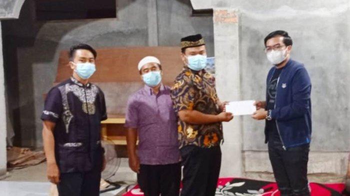 Wakil Ketua DPRD Pekanbaru Ginda Burnama ST (kanan) memberikan cendramata berupa bantuan uang untuk pembangunan Masjid Arafah kepada pengurus, saat silaturahmi di di Masjid Apakah, Perumahan Aura Puri Resident, Jalan Indrapuri Tenayan Raya, Minggu malam (27/12 /2020).