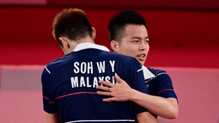 Soh Wooi Yik (kiri) dan Aaron Chia dari Malaysia berpelukan setelah memenangkan pertandingan perempat final bulu tangkis ganda putra melawan Kevin Sanjaya Sukamuljo dari Indonesia dan Marcus Fernaldi Gideon dari Indonesia selama Olimpiade Tokyo 2020 di Musashino Forest Sports Plaza di Tokyo pada 29 Juli 2021 .