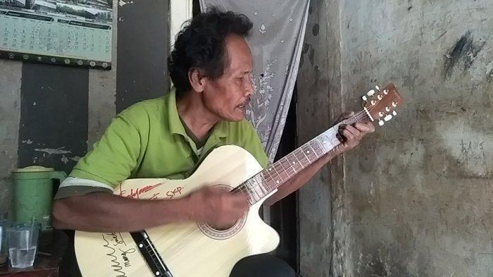Syam Permana dengan sebuah gitar pemberian dari sejumlah pihak yang peduli terhadapnya.