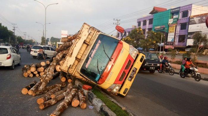 Truk Patah As Roda dan Terbalik di Jalan HR Soebrantas Pekanbaru, Muatan Kayu Berserakan