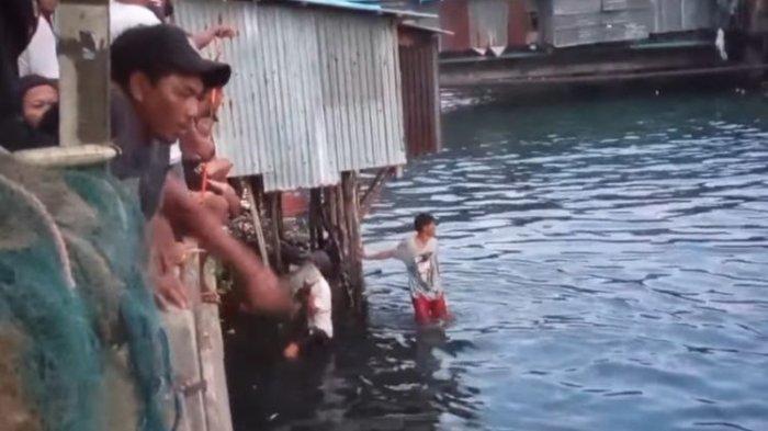 Warga di kawasan Pasar Batu Merah Ambon menangkap kawanan ikan laut bubara yang terjebak di sungai tersebut, Sabtu (1/5/2021)