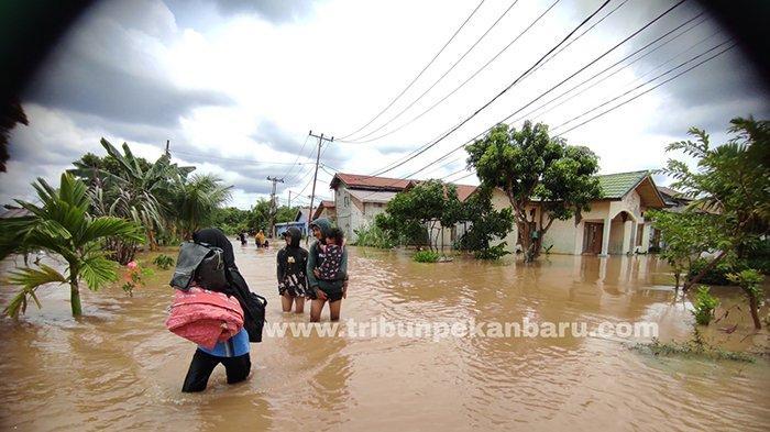 Foto: Warga Angkat Barang Ngungsi di Tengah Genangan Air yang Capai Selutut