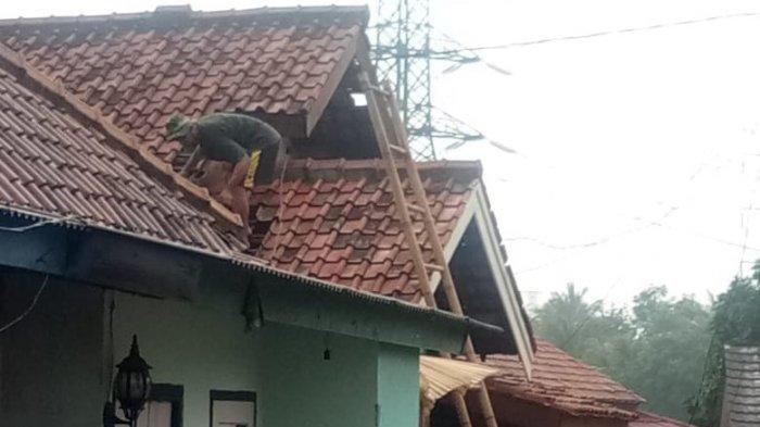 Warga memperbaiki atap yang diterjang angin puting beliung di Kota Cilegon, Jumat (4/6/2021).