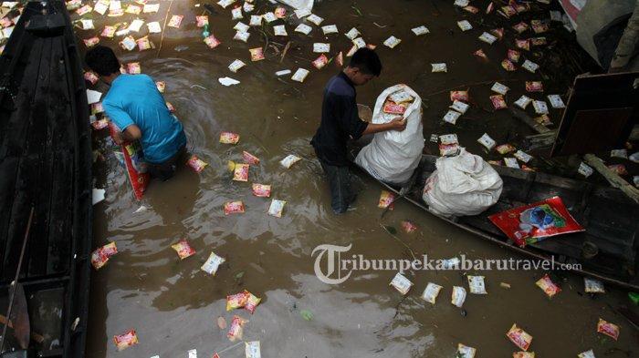 Sejumlah warga mengambil mie instan yang mengambang di pinngiran Sungai Siak, Jalan Pesisir, Kecamatan Pesisir, Pekanbaru, Jumat (15/5/2020).