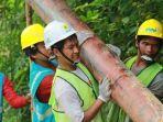 pekerja-pln-mengangkut-tiang-listrik-untuk-pemasangan-jaringan-listrik-di-desa-pedalaman-di-riau.jpg