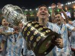 pemain-argentina-lionel-messi-memegang-trofi-saat-ia-merayakan-dengan-rekan-setimnya.jpg