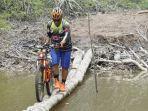 pesepeda-sedang-melintasi-titian-di-atas-sungai-jes-2019-inhil.jpg