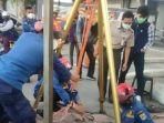 petugas-damkar-evakuasi-kartu-atm-yang-jatuh-ke-saluran-air.jpg
