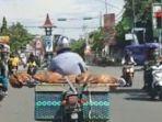 pria-naik-motor-membawa-jenazah-di-atas-beronjong.jpg