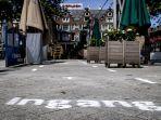 sebuah-tanda-panah-di-tanah-untuk-menjaga-jarak-sosial-di-leidseplein-di-amsterdam.jpg