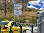 sebuah-taxi-melintas-di-samping-bendera-israel-di-kota-nablus.jpg