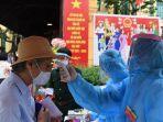 seorang-pekerja-medis-memeriksa-suhu-di-vietnam.jpg