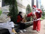 seorang-pria-berkostum-santa-claus-membagikan-kopi-gratis-kepada-warga.jpg