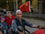 seorang-pria-mengendarai-kendaraan-di-lingkungan-etnik-uighur-di-aksu-xinjiang.jpg