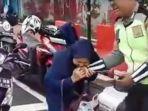 seorang-wanita-tengah-menggigit-petugas-saat-hendak-ditilang_20180222_203145.jpg