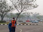 suasana_parkiran_bandara_ssk_ii_diselimuti_kabut_asap.jpg