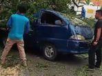 warga-memotong-pohon-tumbang-yang-menimpa-1-unit-kendaraan-di-padang.jpg