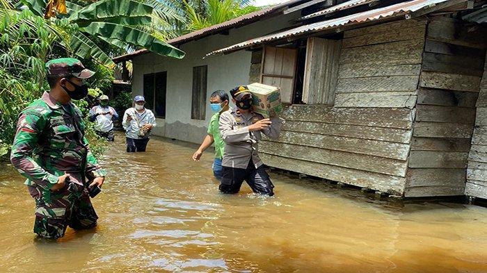 Kapolsek Muara Pawan Terjang Banjir Antar Bantuan Sembako ke Warga