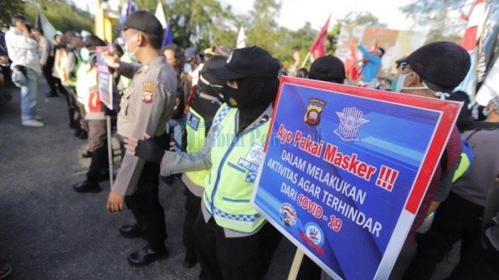 Anggota Polresta Pontianak memegang papan ajakan menggunakan masker saat mahasiswa menggelar damai menolak Omnibus Law di Bundaran Digulis, Jalan Ahmad Yani, Pontianak, Kalimantan Barat, Sabtu 17 Oktober 2020 sore.