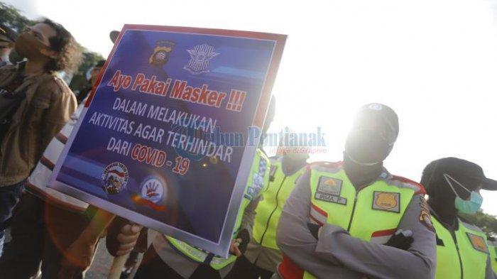FOTO: Personel Polresta Pontianak Pegang Papan Bertuliskan Ajakan Menggunakan Masker di Bundaran