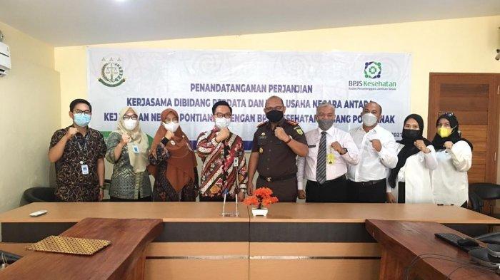 Kepala BPJS Kesehatan Pontianak, Adiwan Qodar foto bersama dengan Kepala Kejaksaan Negeri Pontianak, Basuki Sukardjono, SH MH di kantor sementara Kejaksaan Negeri Pontianak, Rabu 28 April 2021.