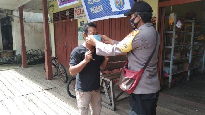 Cegah Penyebaran Covid-19, Personel Polsek Bunut Hilir Bagikan Masker kepada Warga