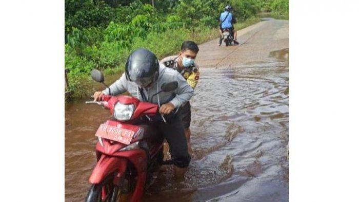 Personel Polsek Bika Lakukan Patroli dan Bantu Warga Melewati Jalan Raya yang Tergenang Banjir