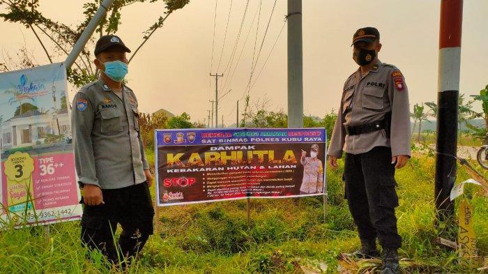 Personil Satuan Binmas Polres Kubu Raya melakukan pemasangan Spanduk Himbauan Bahaya Karhutla di tiga titik di desa yang dianggap rawan terjadinya kebakaran Hutan dan Lahan di wilayah hukum Polres Kubu Raya, Rabu  17 Februari 2021.