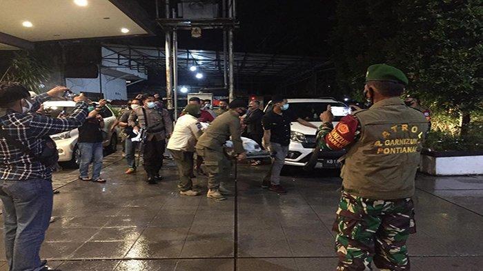 Petugas Gabungan dari Satpol PP Kota Pontianak, Personel Polisi dan TNI saat mengevakuasi YG (38) Perempuan yang nekat terjun dari lantai empat untuk menghindari razia dari petugas pada Jumat, 26 Desember 2020 dini hari.