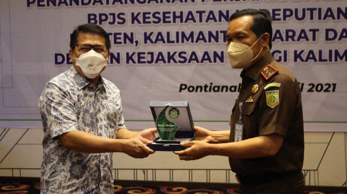 Deputi Direksi Wilayah Bakalbalam BPJS Kesehatan, dr Donni Hendrawan menyerahkan cinderamata kepada Kajati Kalbar, Dr. Masyhudi usai penandatanganan MoU di Ibis Hotel Pontianak, Rabu, 7 April 2021.