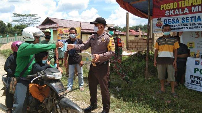 Cegah Penyebaran Covid-19, Bhabinkamtibmas Bagikan Masker kepada Warga Desa Setia Budi