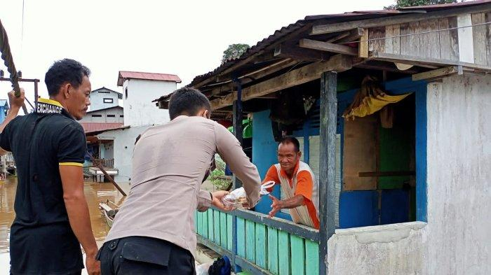 Bhabinkamtibmas Polsek Ella Hilir Bripda Ilham Maulana mendampingi Kepala Desa Domet Permai Zulkarnaen dan perangkat desa membagikan sembako kepada masyarakat yang terdampak banjir di Desa Domet Permai Kecamatan Ella Hilir Kabupaten Melawi, Senin 4 Oktober 2021.