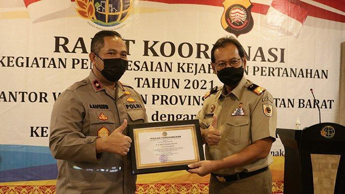 Kepala Kantor Wilayah Badan Pertanahan Nasional (BPN) Kalbar, Ery Suwondo  saat menyerahkan penghargaan kepada Tim Satgas Mafia Tanah Polda Kalbar di Hotel Golden Tulip Pontianak, Rabu 16 Juni 2021.