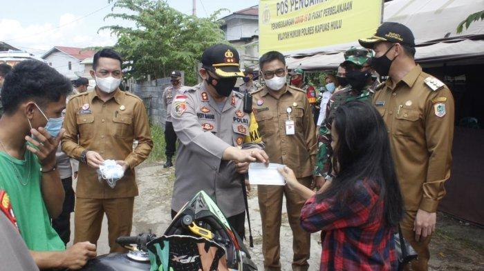 Kapolres Kapuas Hulu AKBP Wedy Mahadi S.I.K., M.A.P, serta Forkopimda Kabupaten Kapuas Hulu bagikan masker kepada warga, Selasa 11 Mei 2021.