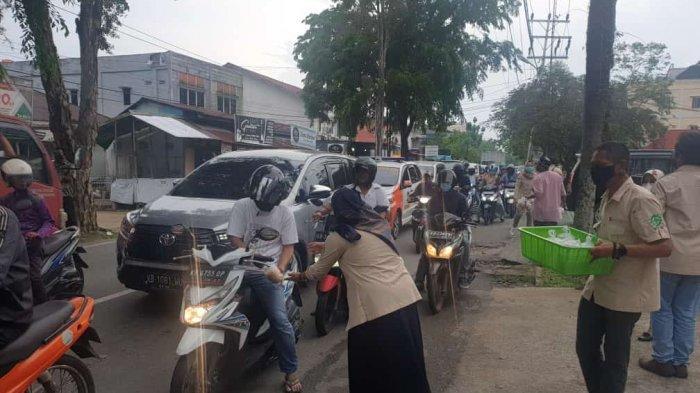 Karyawan LO Pontianak membagikan takjil dan masker bagi pelintas di Jalan Urai Bawadi Pontianak.