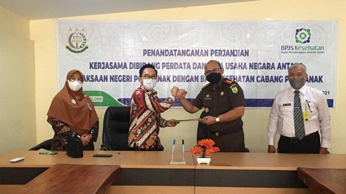 Kepala BPJS Kesehatan Pontianak, Adiwan Qodar teken kerjasama dengan Kepala Kejaksaan Negeri Pontianak, Basuki Sukardjono, SH MH di kantor sementara Kejaksaan Negeri Pontianak, Rabu, 28 April 2021.