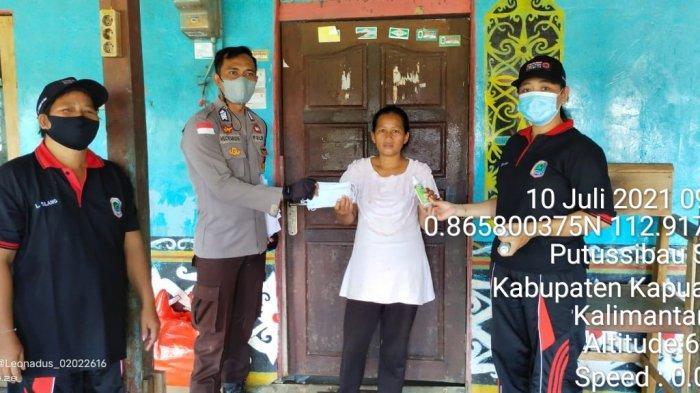 Personel Polsek Putussibau Selatan bagikan masker kepada warga, Sabtu 10 Juli 2021.