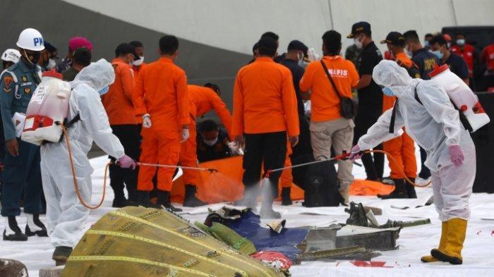 Petugas menyemprotkan cairan disinfektan ke bagian pesawat Sriwijaya Air SJ182 rute Jakarta - Pontianak yang jatuh di perairan Pulau Seribu di Dermaga JICT, Tanjung Priok, Jakarta Utara, Minggu (10/1/2021). Temuan bagian pesawat selanjutnya akan diperiksa oleh KNKT sedangkan potongan tubuh korban diserahkan kepada DVI Polri untuk identifikasi lebih lanjut.
