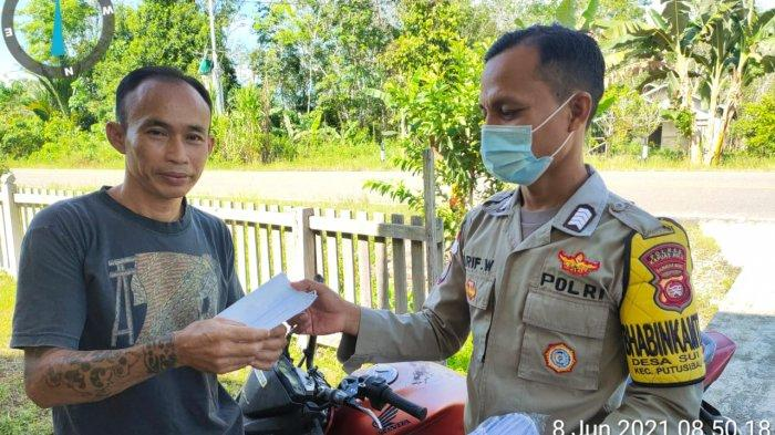 Bhabinkamtibmas Polsek Putussibau Selatan bagikan masker kepada warga di desa binaannya, Selasa 8 Juni 2021