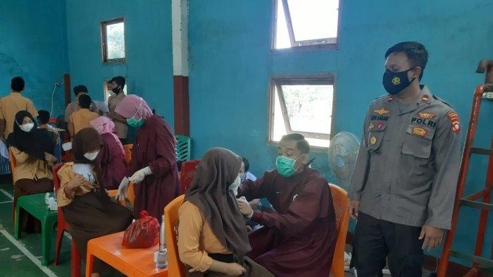 Kapolsek Sajad, IPDA Agus Ganjar N melakukan pengamanan dan monitoring pelaksanaan Vaksinasi Covid-19 kepada pelajar SMP Negeri 2 Sajad di Gedung Serba Guna Kecamatan Sajad Kabupaten Sambas, Jumat 8 Oktober 2021 sekitar pukul 08.00 Wib.