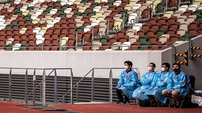 Petugas berpakaian pelindung dan masker, di Stadion Nasional di Tokyo, Jepang, 11 Mei 2021. Olimpiade Tokyo 23 Juli hingga 8 Agustus 2021 dipusatkan di stadion ini dengan protokol kesehatan yang sangat ketat.