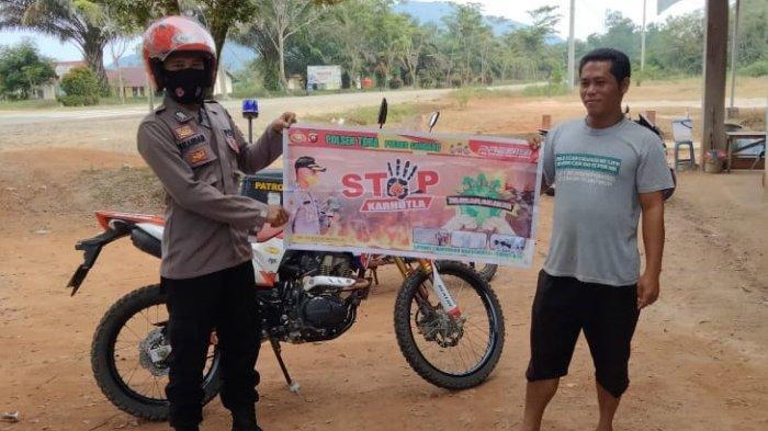 Anggota Polsek Toba Bripka Iskandar melaksanakan kegiatan Patroli Rutin untuk mengkampanyekan stop karhutla dengan menggunakan spanduk, Jumat 8 Oktober 2021.