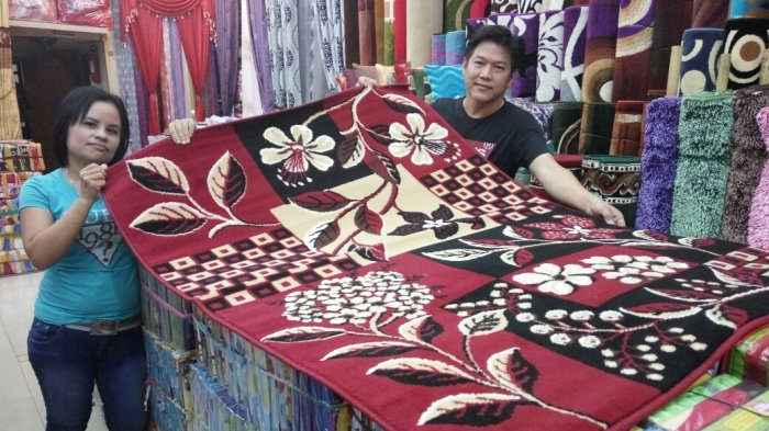 Pemilik Toko Anugerah Gorden Hasan (50) dan karyawatiny, berpose pamerkan satu dari beberapa motif karpet Belgia yang dijual di tokonya itu, Selasa (22/03/2017).