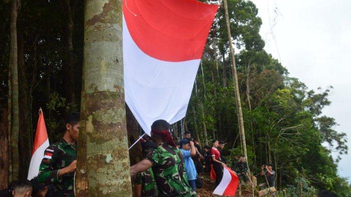 Satgas Yonmek 643/Wns Kibarkan Merah Putih Raksasa di Puncak Entinyuh