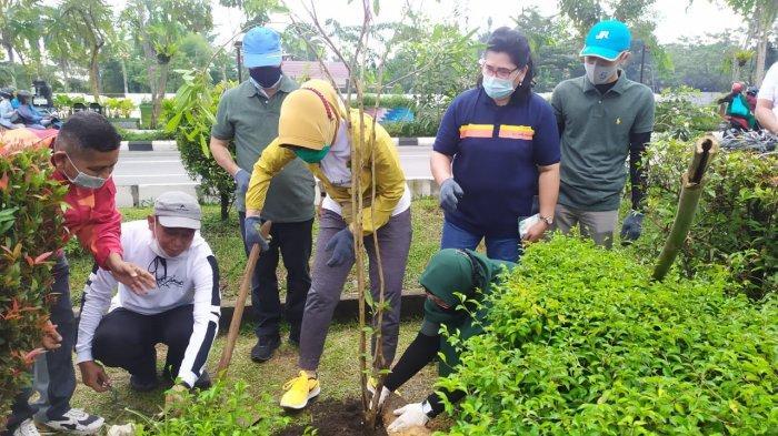Istri Wali Kota Pontianak, Yeni Kamtono menanam pohon Tabebuya bersama Kepala Unit Keuangan, Akuntansi dan PKBL, Silvia Desri di kawasan Taman Catur, Pontianak, pada Jumat, 27 November 2020.